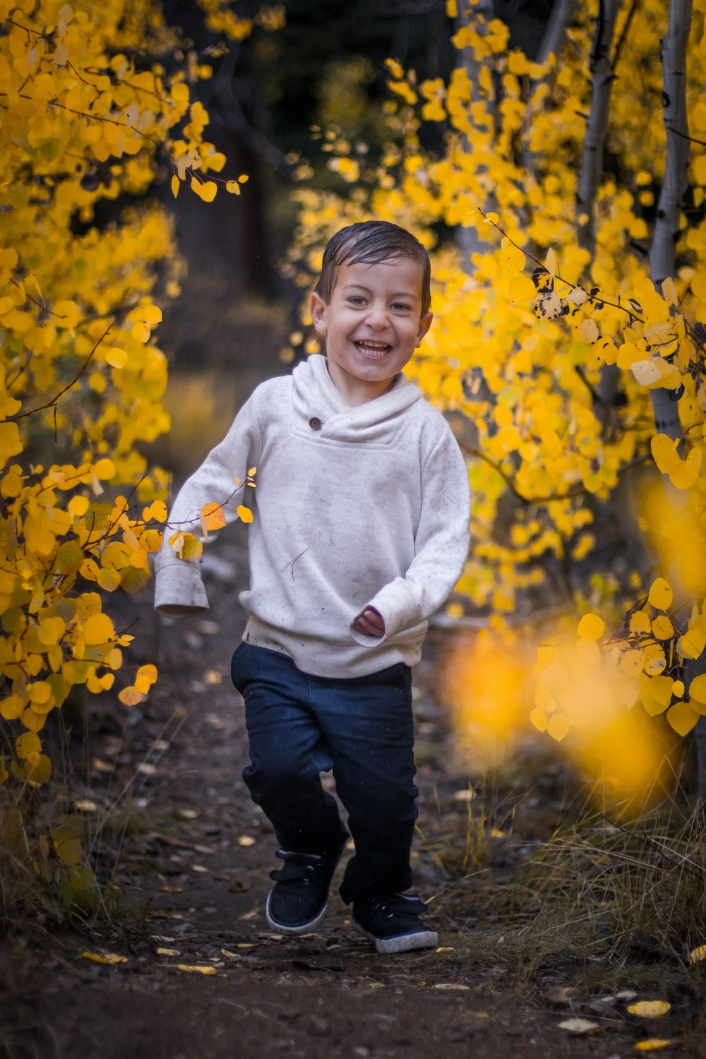 boy in white pullover hoodie and blue denim jeans running on dirt pathway beside yellow leaves plant