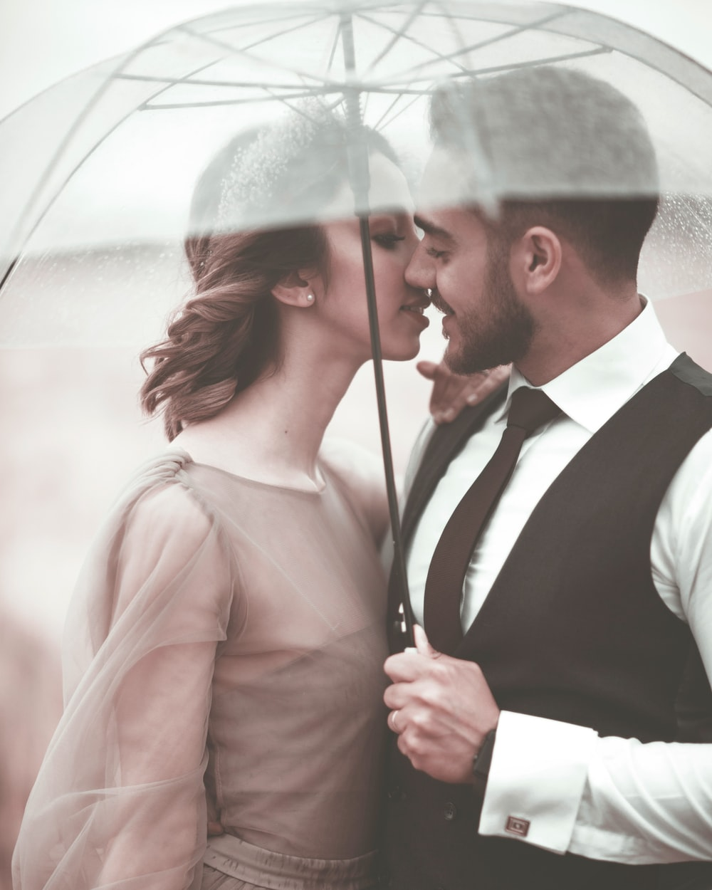woman and man about to kiss under umbrella