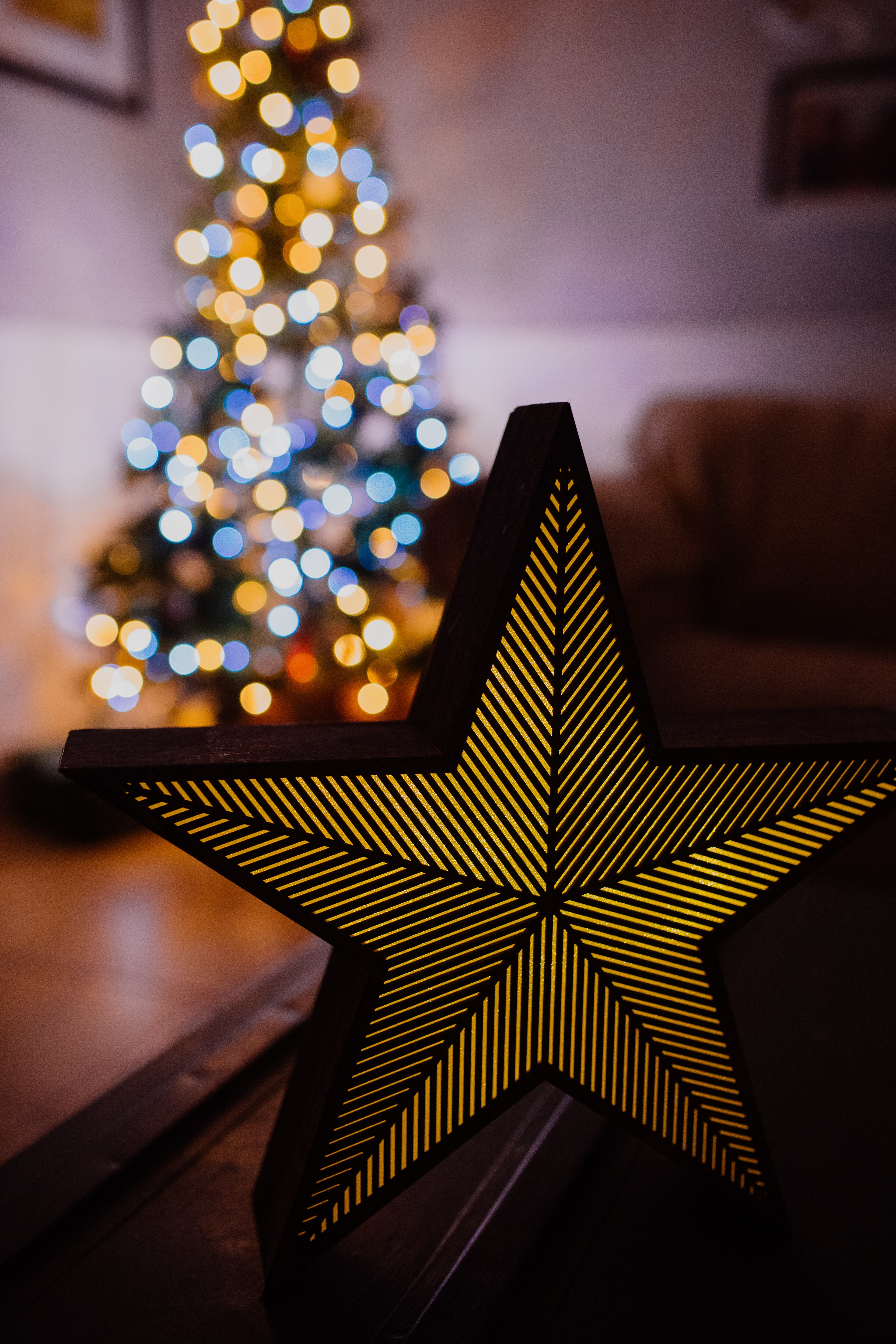 gold and black star near lit Christmas tree