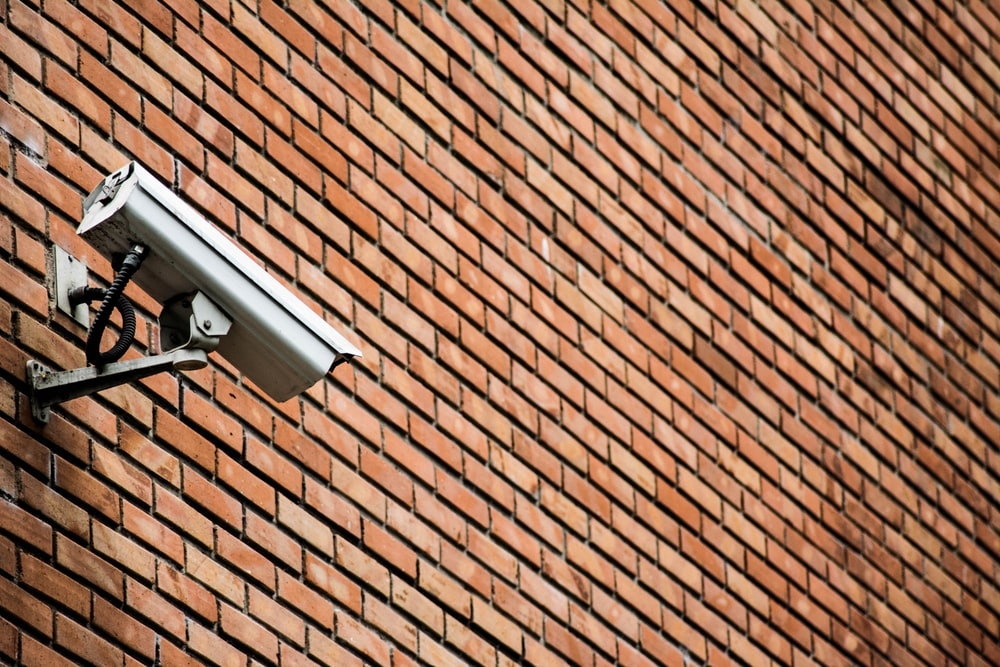 white CCTV on brown brick wall