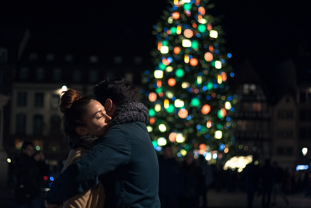 selective focus photography of man and woman hugging each other near Christmas tree
