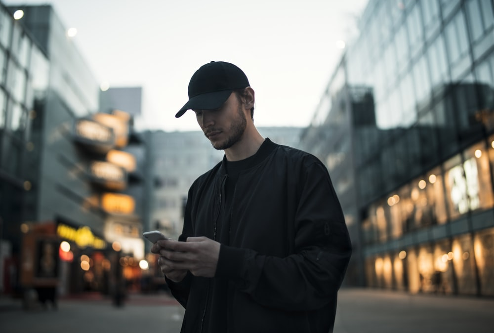 man in black jacket wearing black fitted cap while using phone