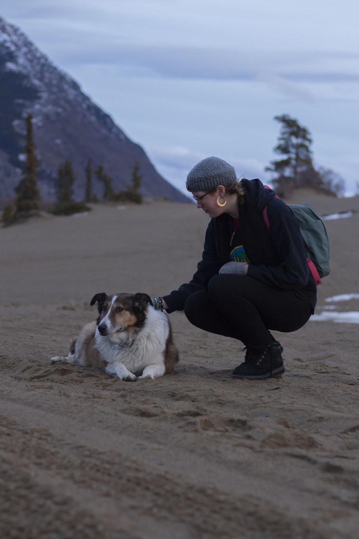 woman holding dog lying on ground
