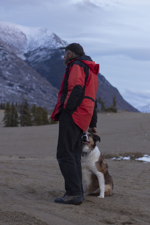man wearing red jacket standing beside dog
