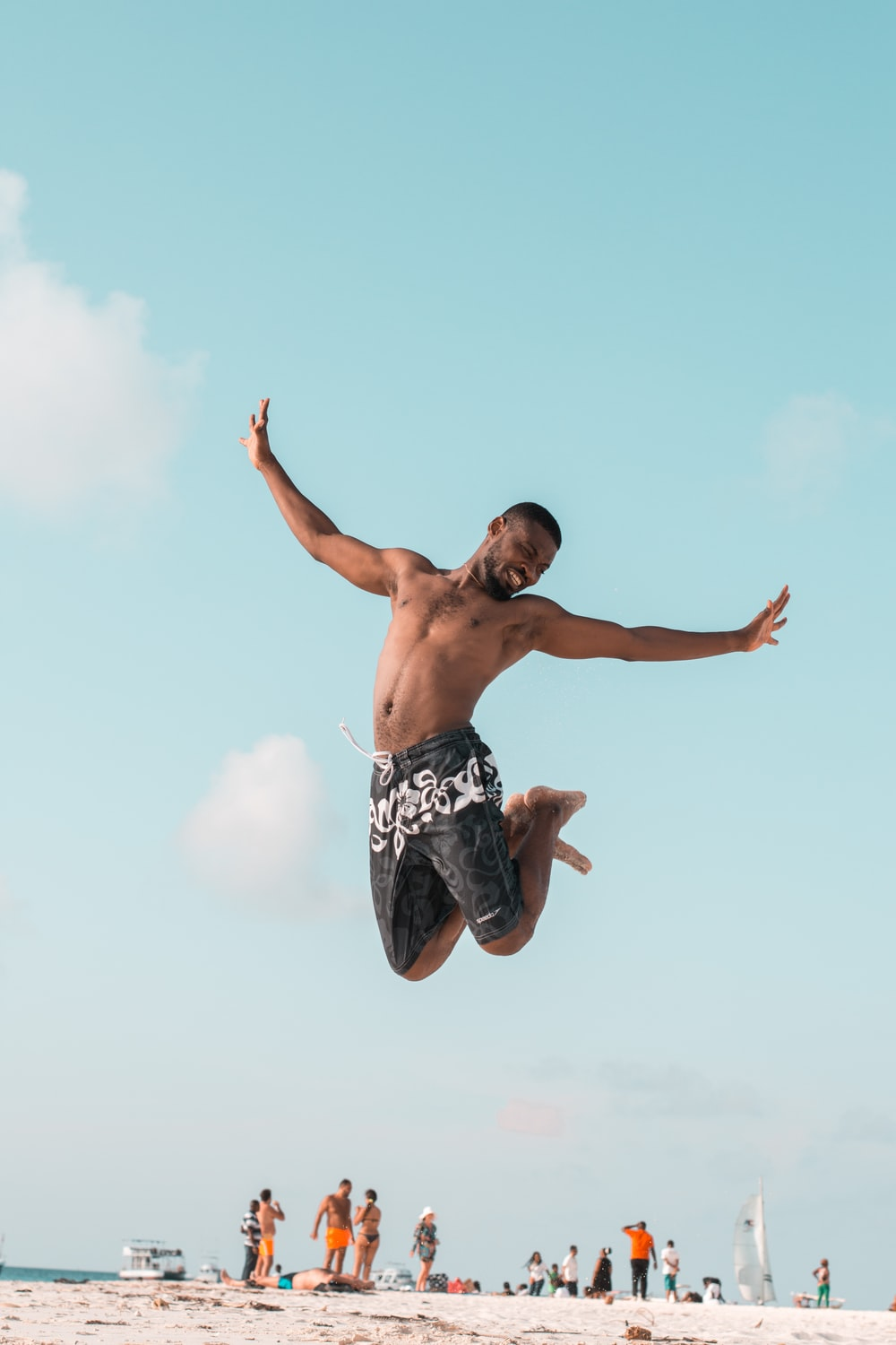 man jumping while spreading his arms and folding his legs at the beach during day