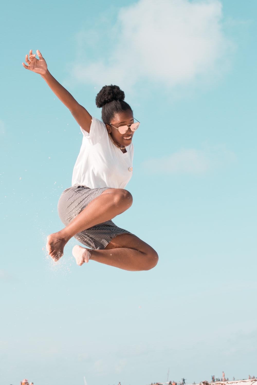 woman jumping wearing white shirt during daytime