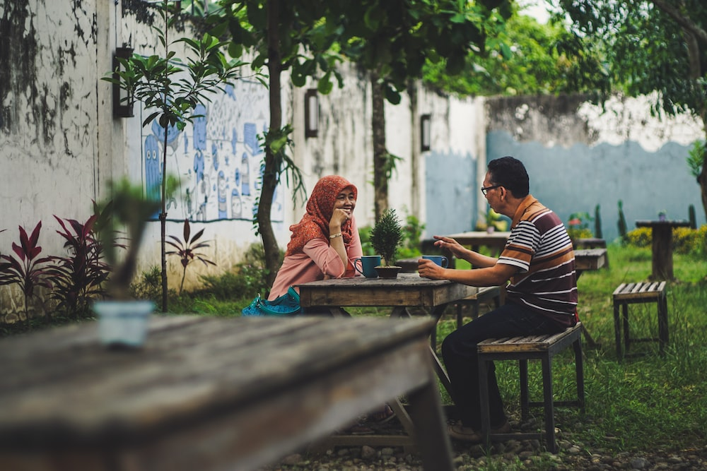 man and woman sitting beside table