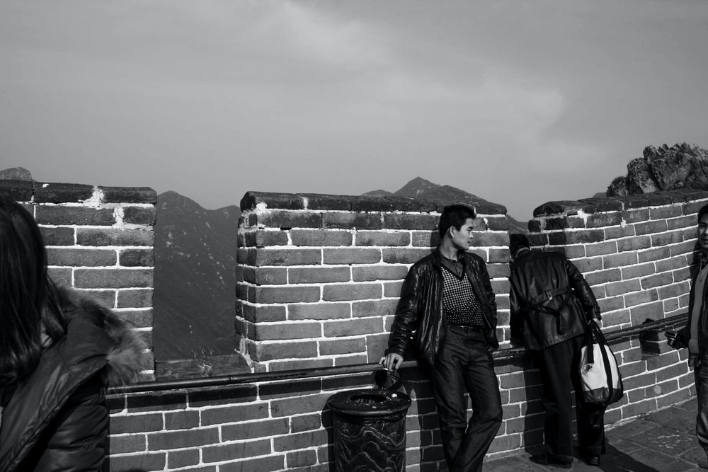 grayscale photography of man standing beside brick wall