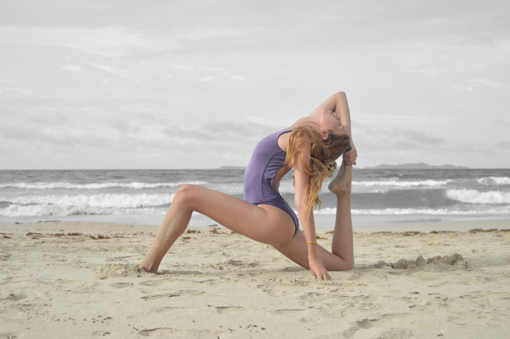 woman doing stretches on beach shore