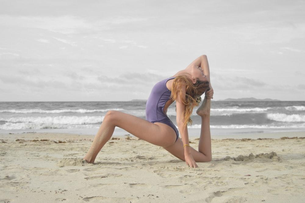 woman doing ballet stunt on beach shore
