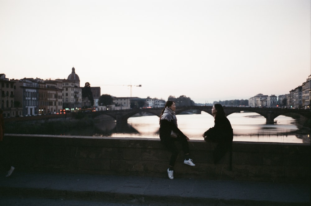 two person sitting on bridge