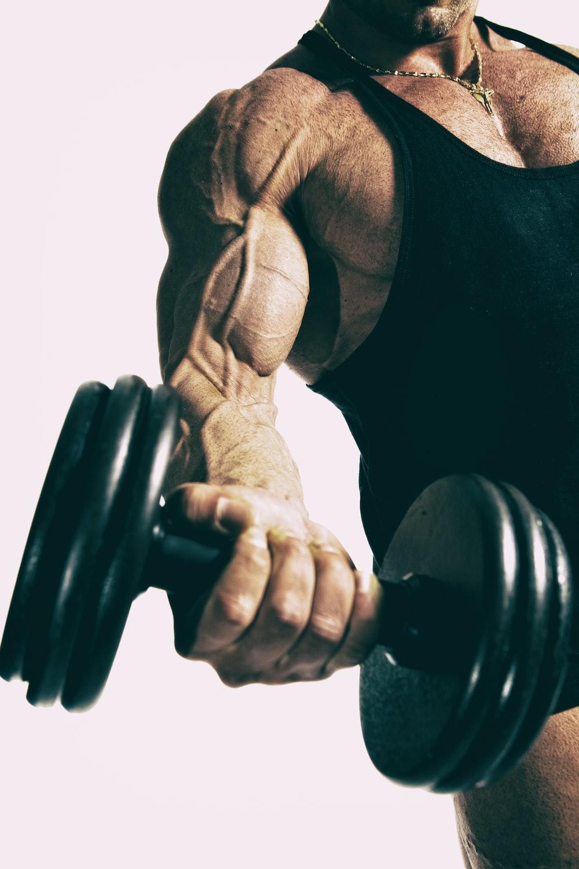 man lifting black dumbbell