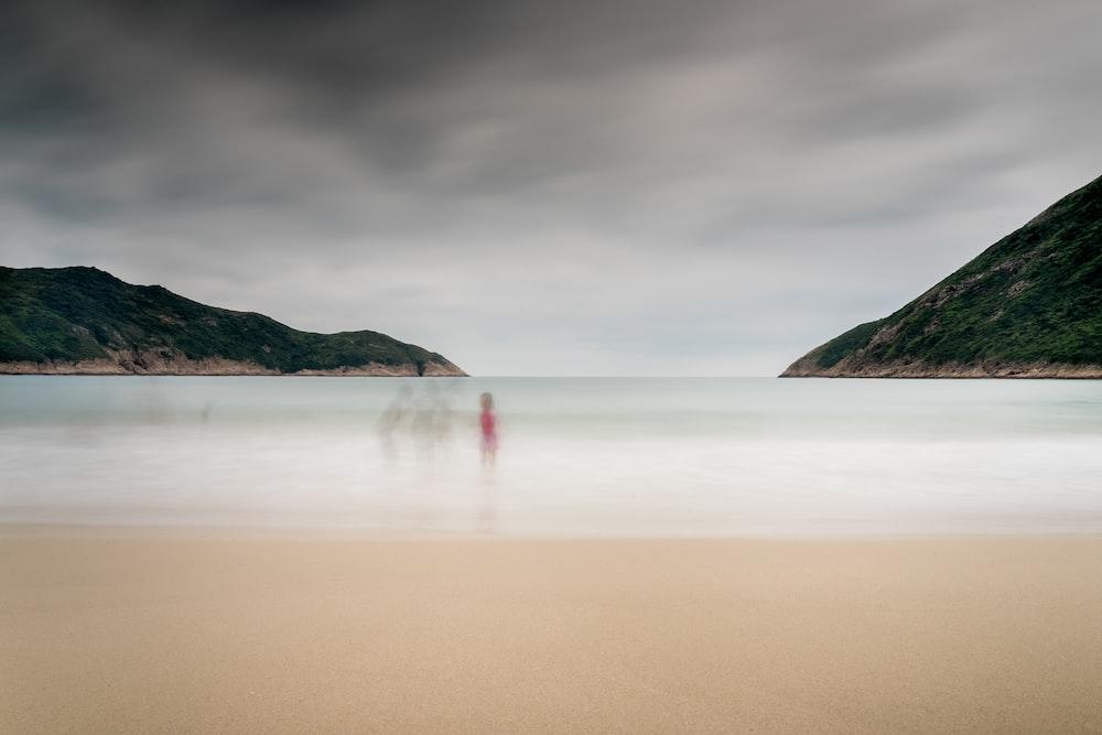 toddler standing on seashore near mountain range