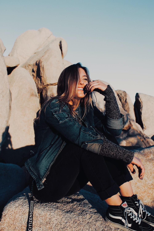 sitting and smiling woman wearing black pants