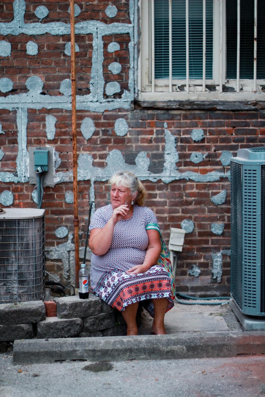 woman sitting on concrete brick curb
