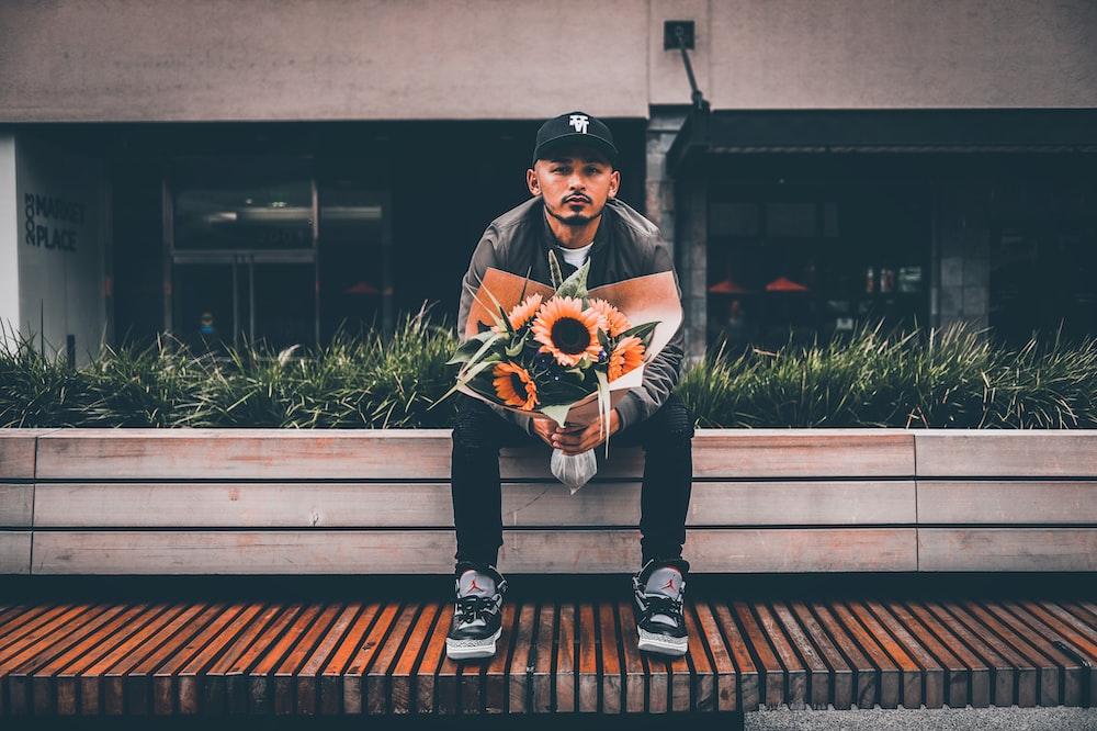 sitting man holding sunflower bouquet