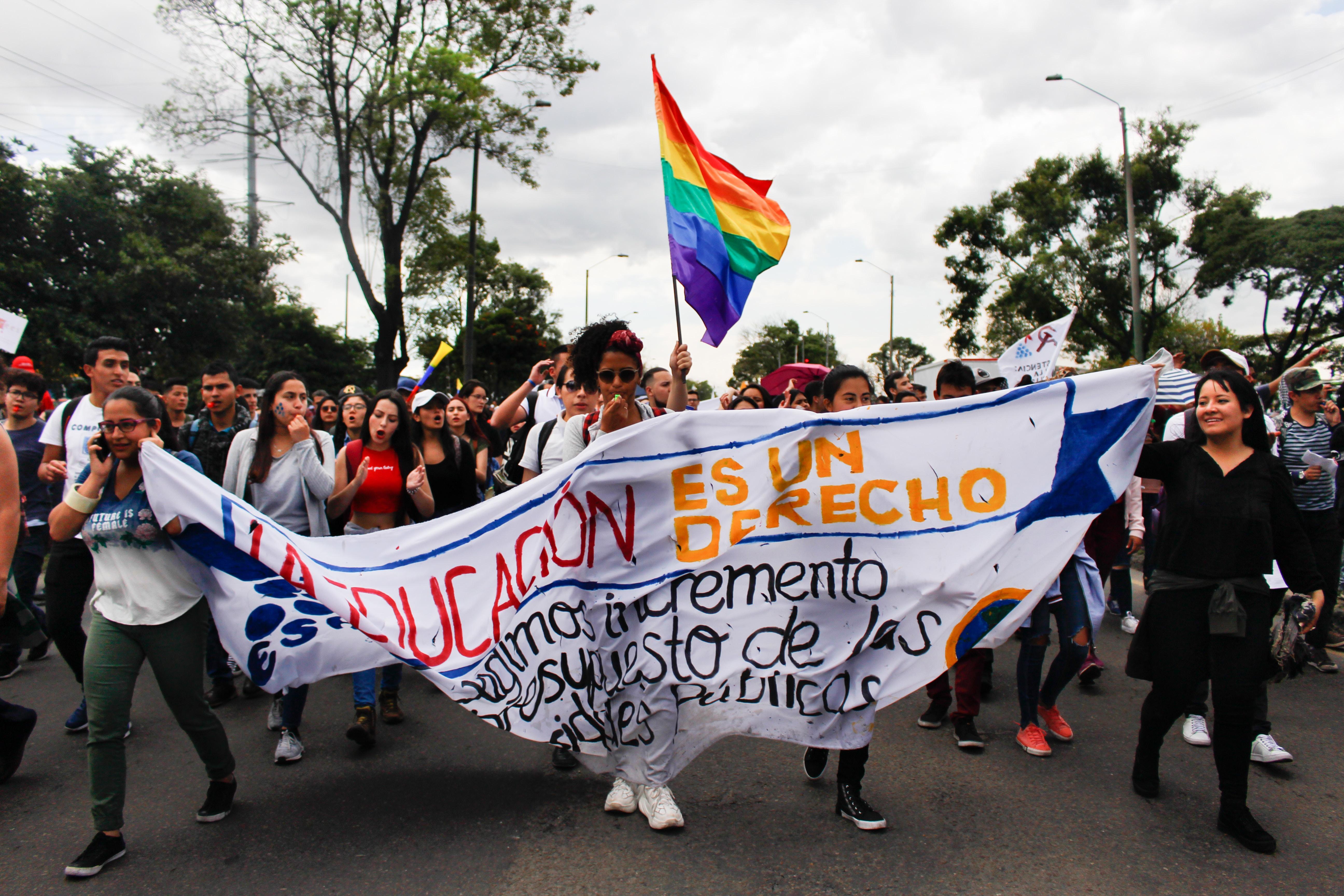 group of people walking on street holding Rainbow flag