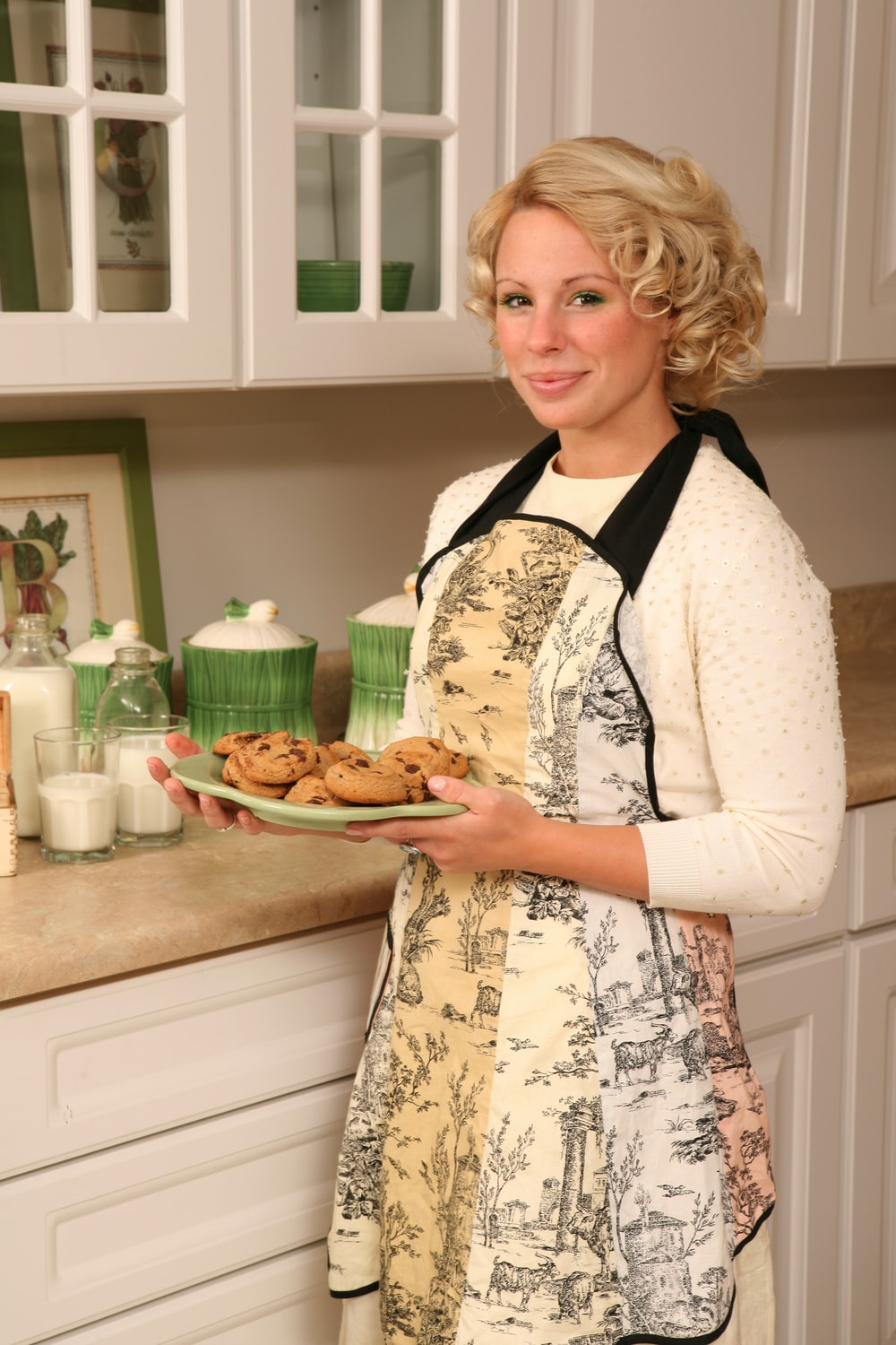 woman holding white plate with cookies