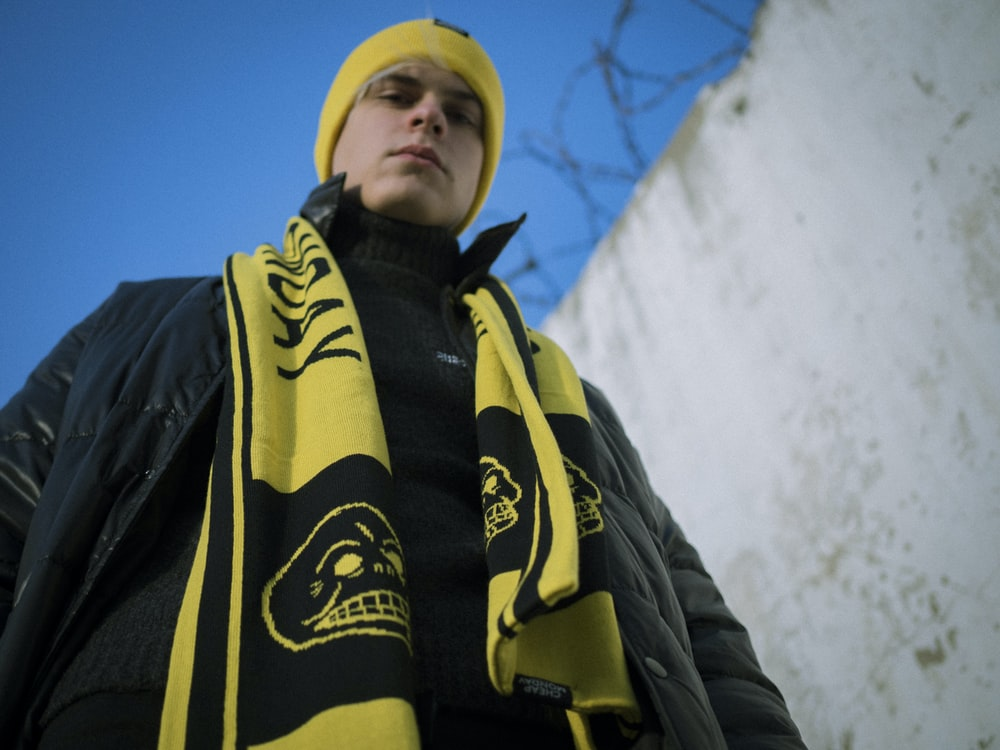 man wearing black leather jacket with yellow and black scarf