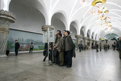 group of men standing beside signage north korea zoom background