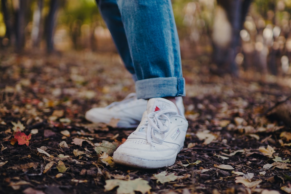 person in blue jean and white sneaker