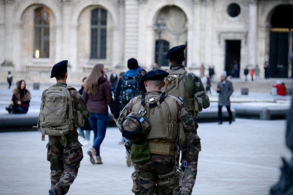 昼間の建物の近くの軍服の男性