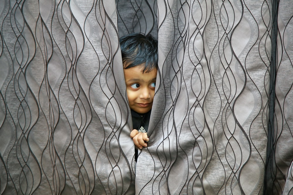 boy hiding behind of gray textile