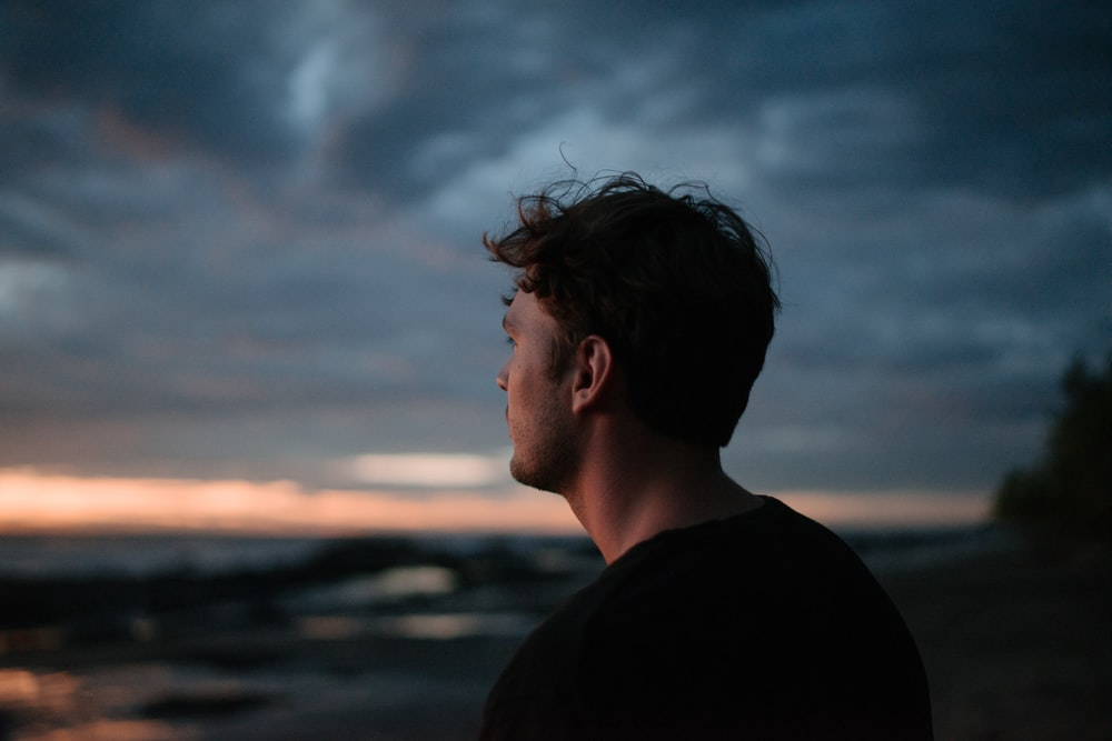 selective focus photography of man under cloudy sky