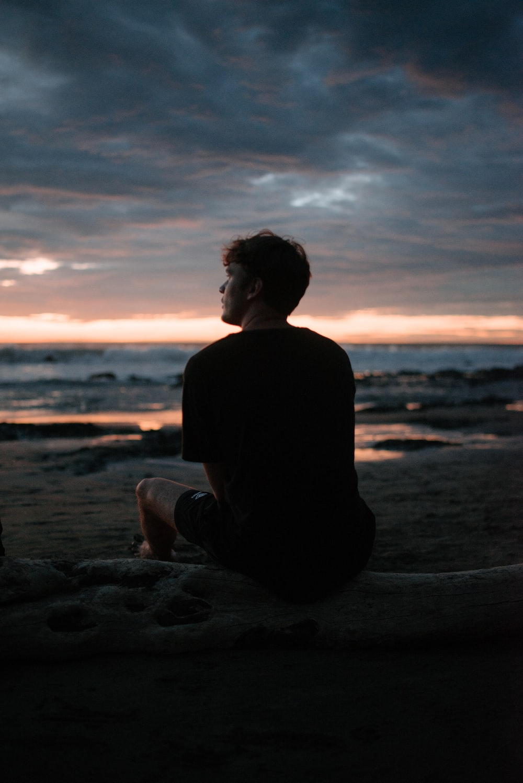 silhouette photo of man sitting on beach