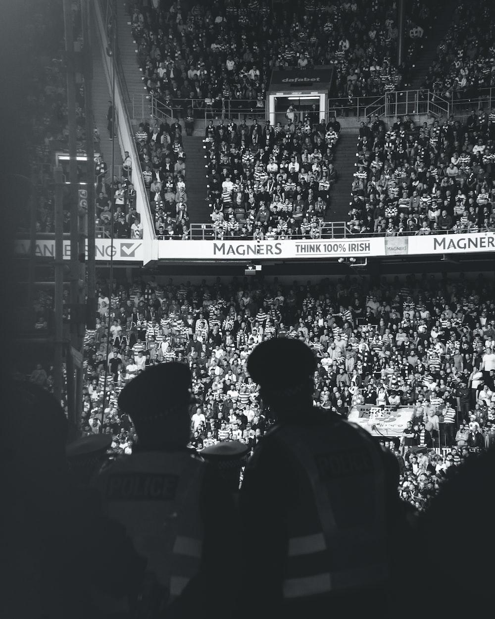 grayscale photo of men in stadium