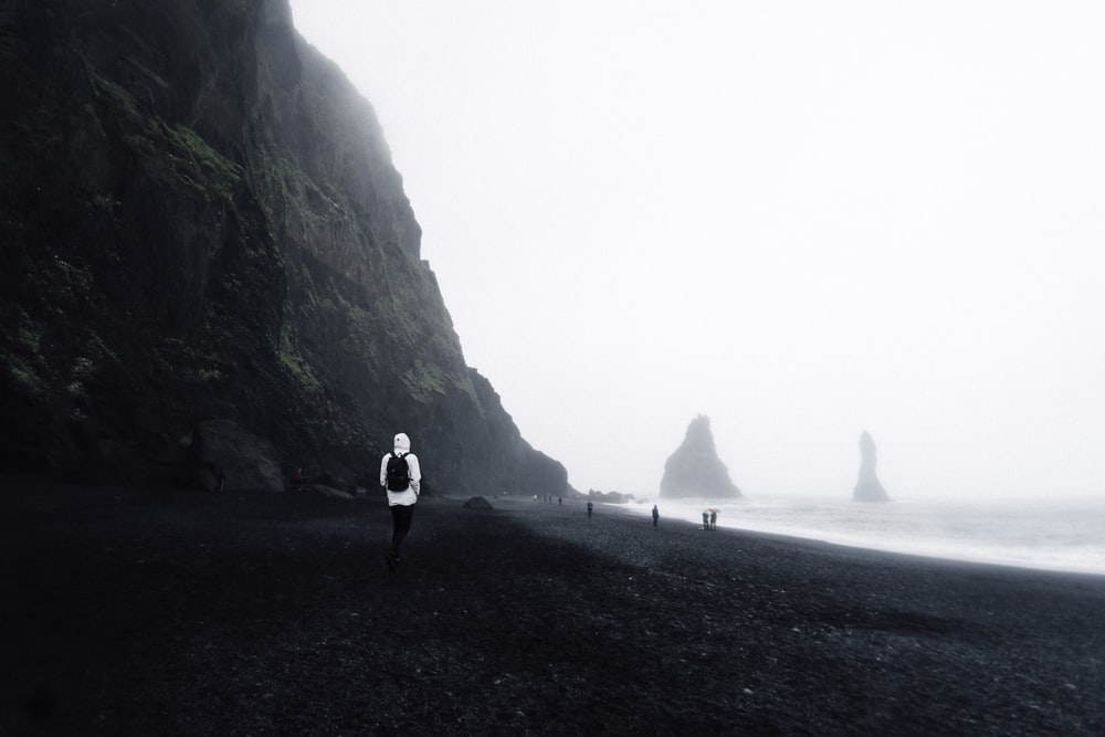 person wearing white hoodie standing on sands
