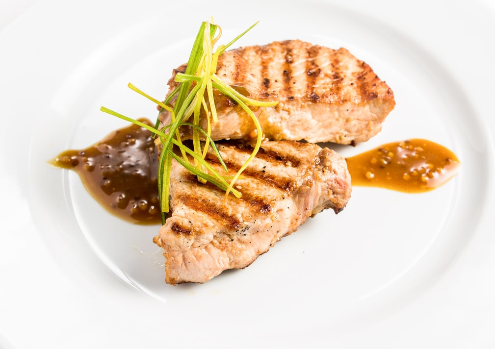 Grilled meat with sauce on a white plate