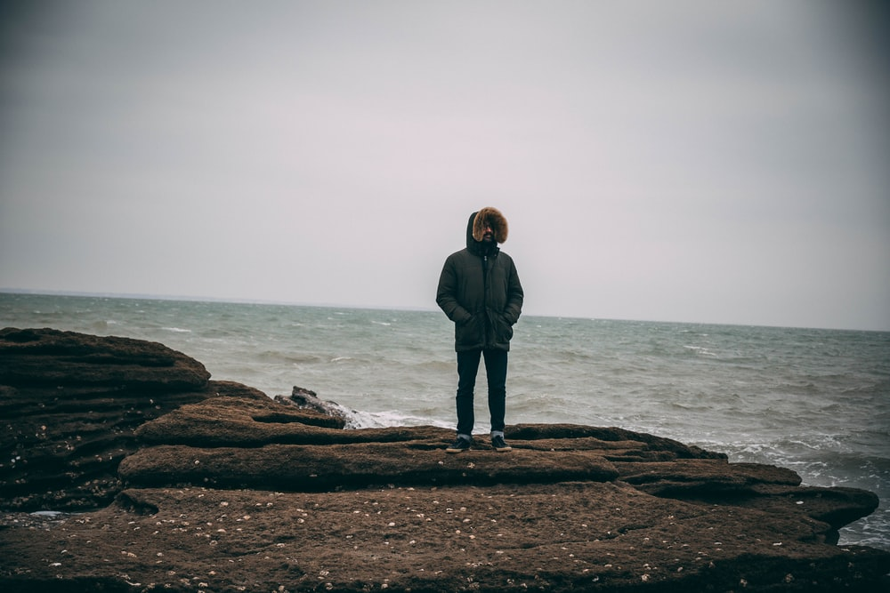 man in parka jacket standing by the sea