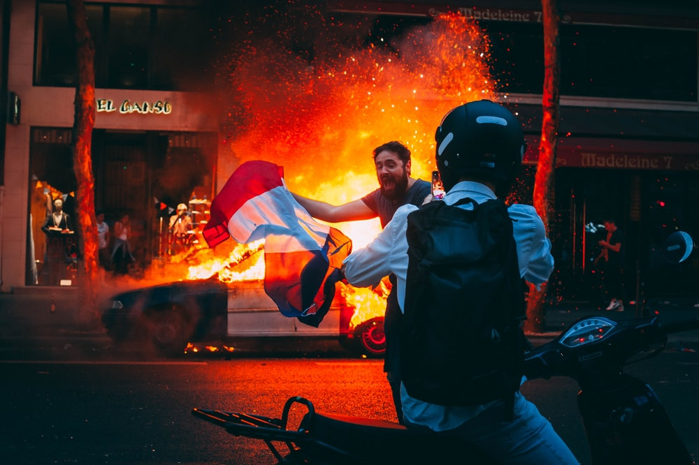 men in front of burning car