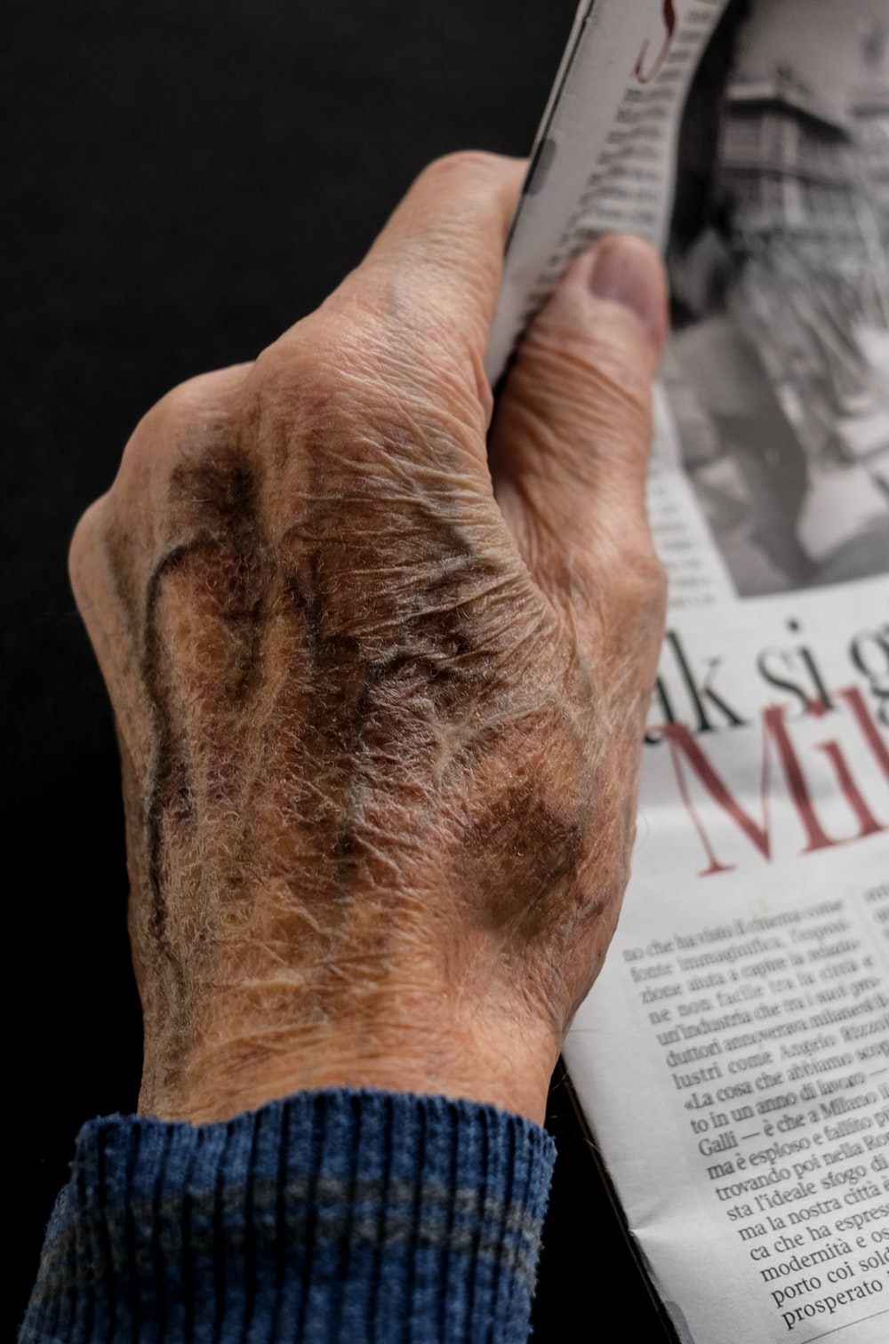 man wearing blue long sleeve top holding newspaper