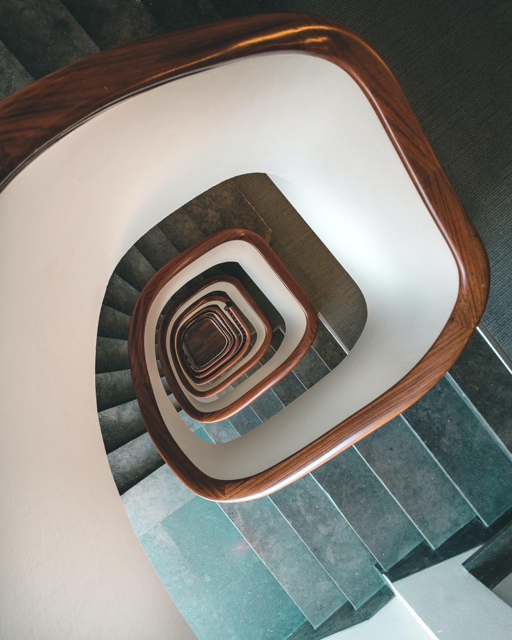 white spiral staircase with brown wooden railings