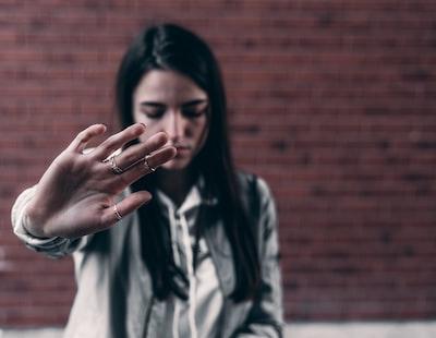 右手を前に突き出して拒絶している若い女性の写真