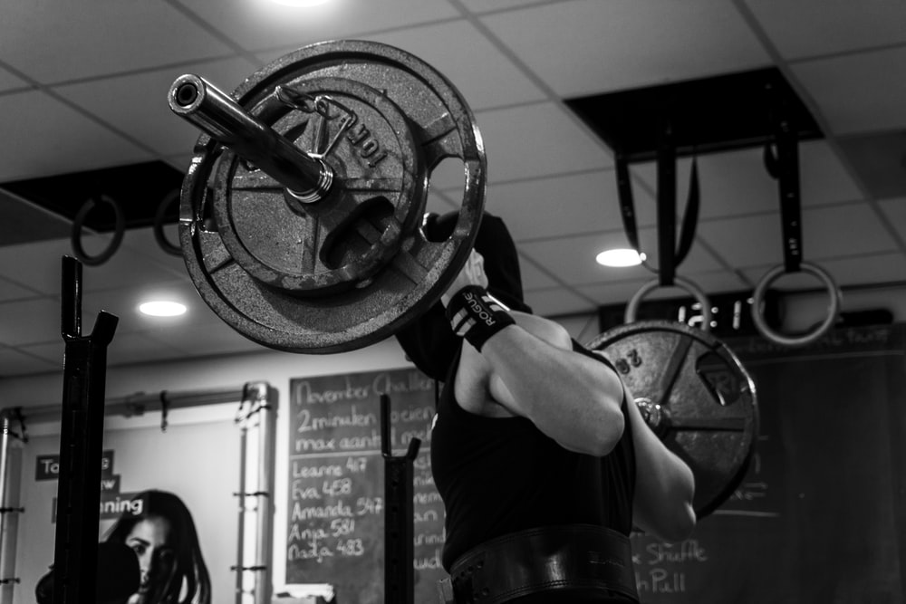 grayscale photo of man lifting barbell