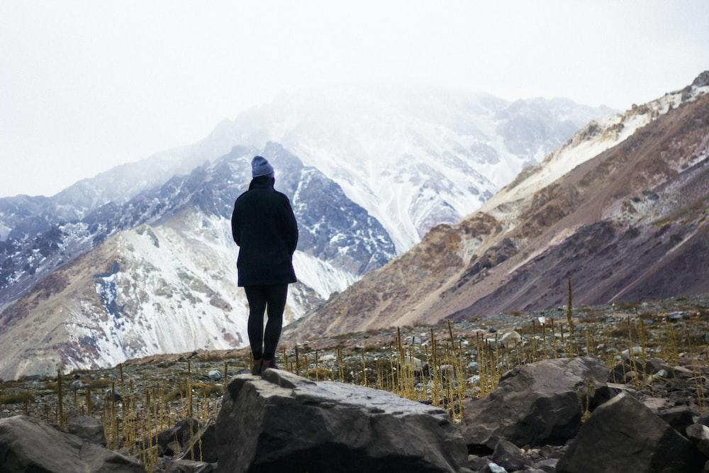 man standing near rock facing mountains