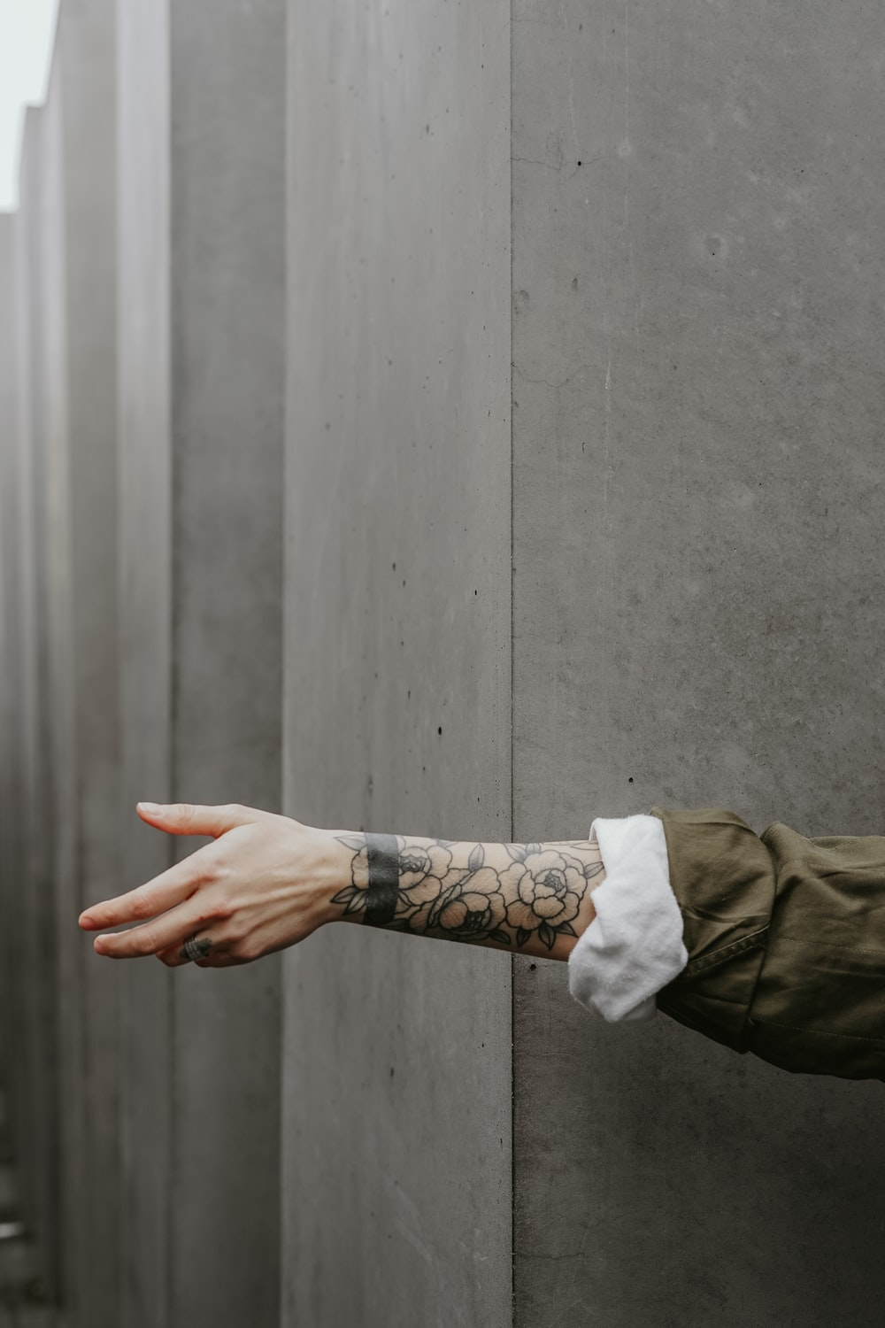 person in green long-sleeved shirt showing tattoo