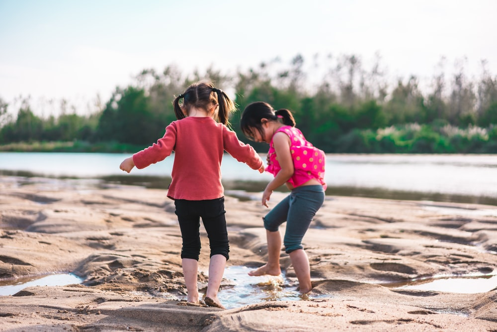 shallow focus photo of girls playing in sand during daytime