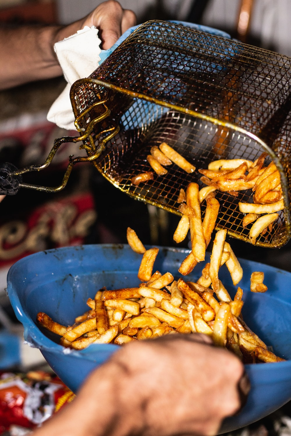 person transferring fries from basket to a bowl