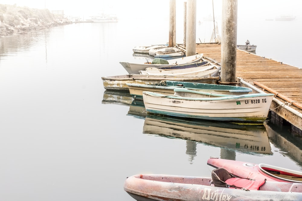 kayak and boats beside wooden dock