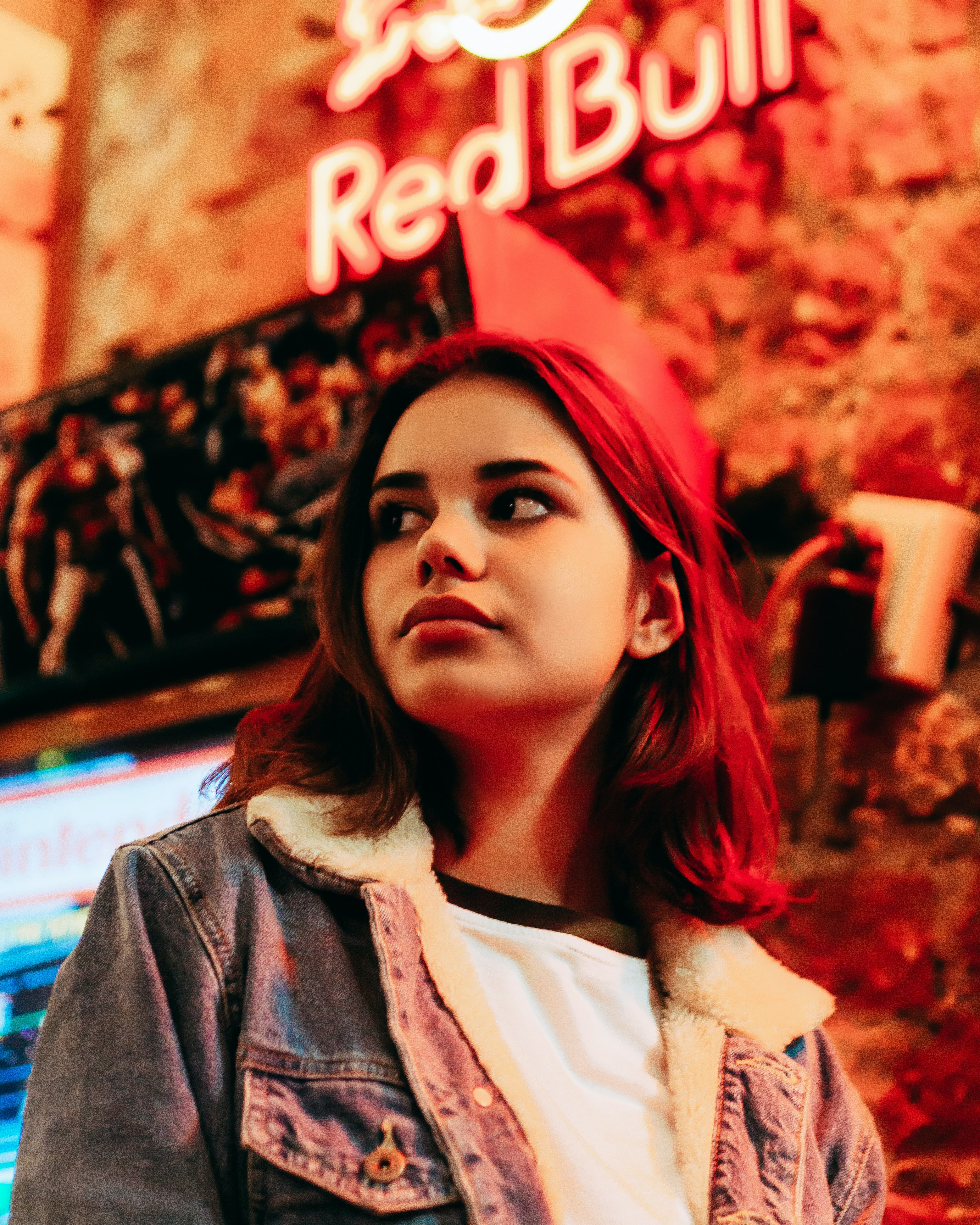 woman wearing blue denim jacket standing near the Red Bull neon light signage