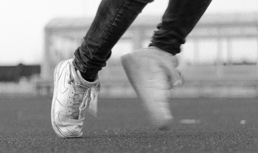 greyscale photo of person wearing Nike lace up shoes