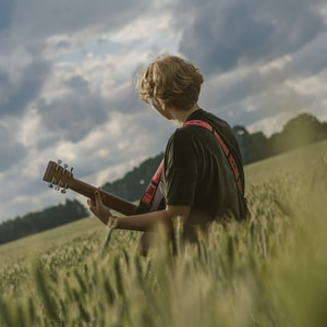 man paying guitar in the middle of green field during daytime