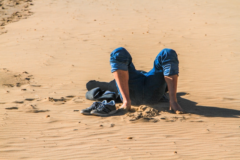 person lying on sand dune