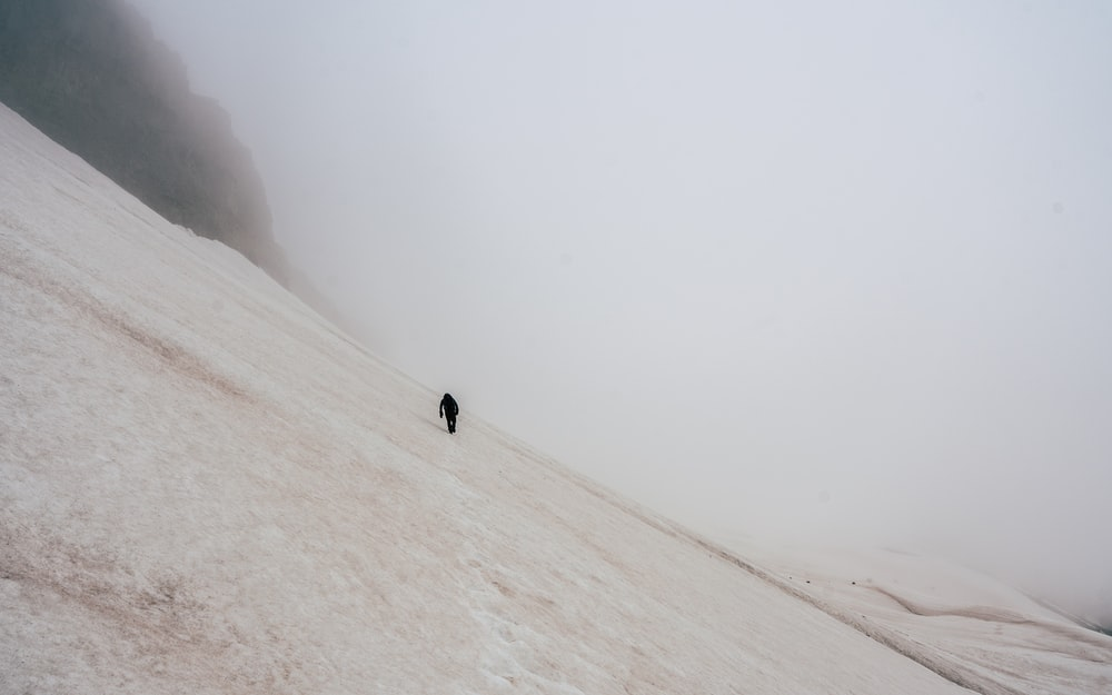 man walking on snow-covered field