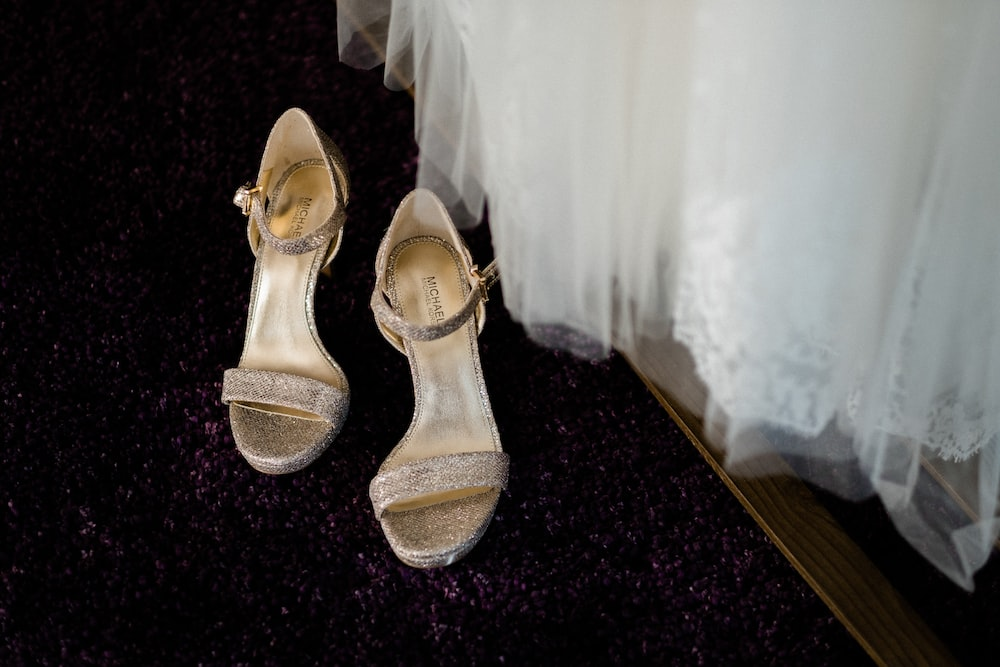 pair of gray and beige leather open-toe ankle-strap heels on the floor