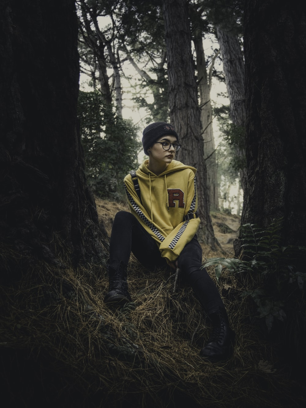 woman wearing yellow pullover hoodie sitting under tree during daytime